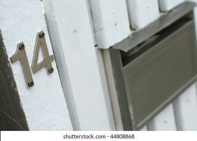 number fourteen sign for home with mailbox on white picket fence