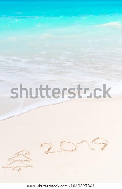 number handwritten on sandy beach with soft ocean wave on background