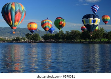Number of hot air balloons launching over a lake in Colorado Springs, Colorado