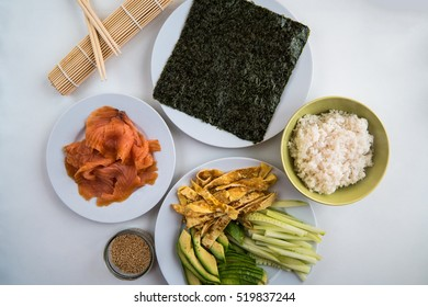 A number of ingredients on plates ready to make sushi