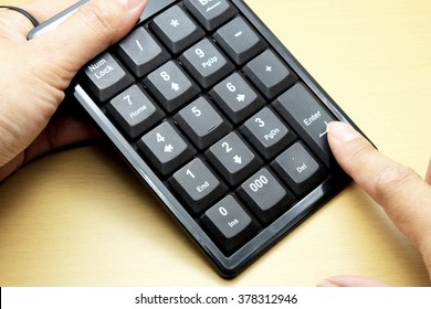 Number keyboard of computer on wooden floor/table, female hand and pressing finger on Enter button. Space for texts.