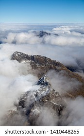 A number of mountain peaks breaking through the clouds in Fjiordland, South Island, New Zealand, from the air on a flight from Milford Sound to Wanaka.