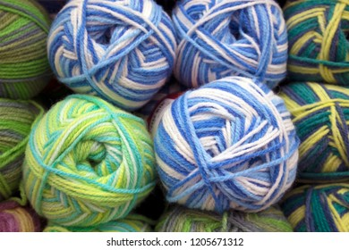 A number of multicolored woolen skeins arranged in rows on a store shelf, yarn texture