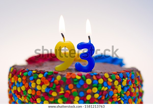Number ninety-three candle lit on top of a chocolate confetti cake