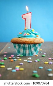 Number one birthday candle on a blue cupcake on blue background