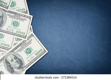 A number of one hundred US dollar notes on a blue chalkboard