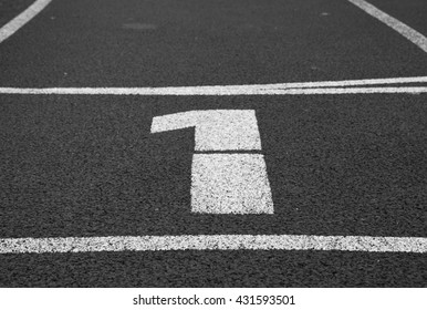 Number one. White track number on red rubber racetrack, texture of running racetracks in small stadium.  Black and white photo
