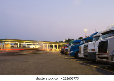 Number of semi trucks of various models and colors in the future on the night truck stop with a lit gas station and blurred lights of a passing semi truck and reflection of the lights on the big rigs.