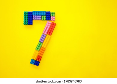 The number seven from the children's multi-colored constructor on a yellow background. Empty space for the text.Holiday date.
