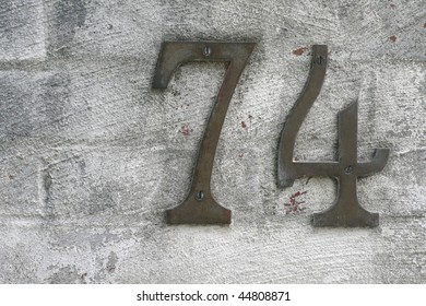 number seventy four for home address against textured brick wall