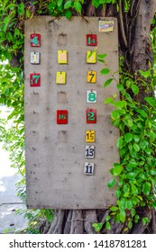 Number sign of Motorcycle queue - Multicolored number signs on brown wood panels next to trees,The current transportation system of Thailand