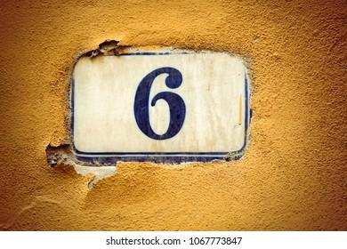 Number six enamel door number on plaster wall