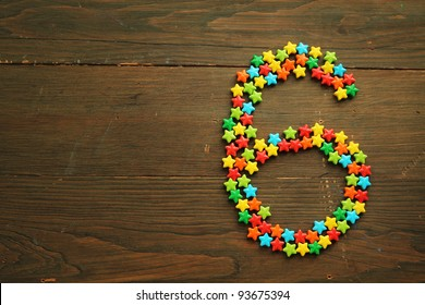Number six made with star shape candies on a wooden table