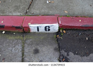 Number Sixteen Painted on Red Curb