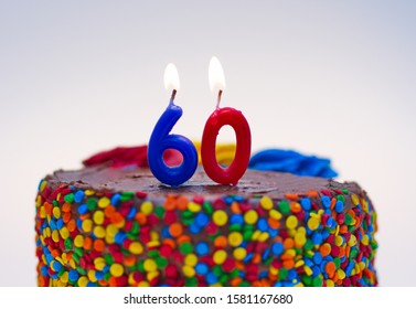 Number sixty candle lit on top of a chocolate confetti cake