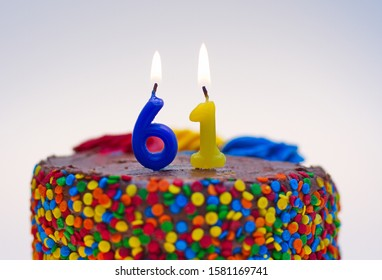 Number sixty-one candle lit on top of a chocolate confetti cake