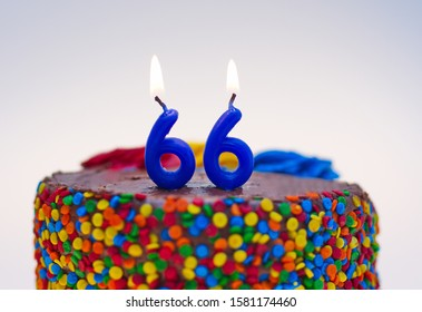 Number sixty-six candle lit on top of a chocolate confetti cake