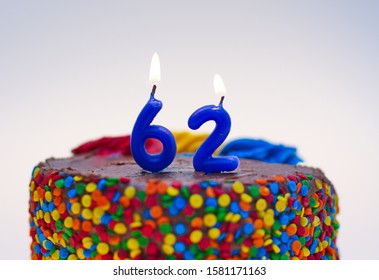 Number sixty-two candle lit on top of a chocolate confetti cake