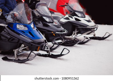 Number of snowmobiles of blue, black, white colour stand on snow. Concept Walking through mountains.