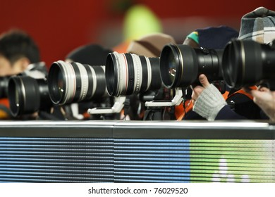 A number of super telephoto lenses in use for a sporting event.