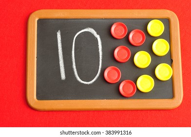 A number ten written on a black board with the same quantity showed by colorful round tokens