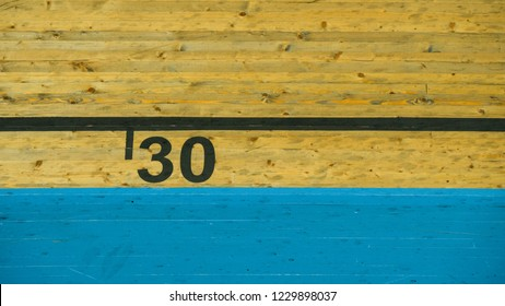 Number thirty (30) in black lettering on vintage, moody wooden texture with blue stripe beneath it.