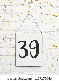 Number thirty nine 39 years old birthday congratulations text with golden confetti sign white brick background