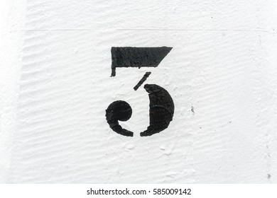 Number three (3) stencil painted on a white background