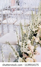 A number of transparent designer chairs at the wedding ceremony alongside beautiful floral arrangements of roses and buttercups