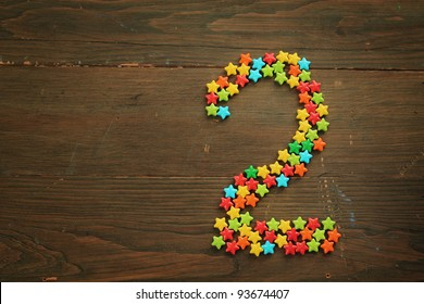 Number two made with star shape candies on a wooden table