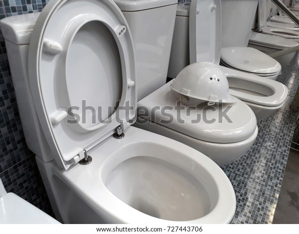 A number of white toilet bowls in the store and white construction helmet on top of one of them