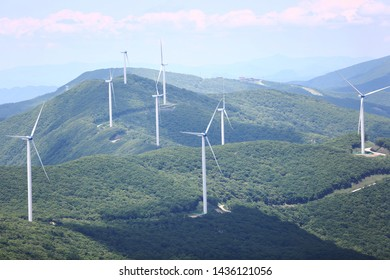 a number of wind generators on high mountainside.