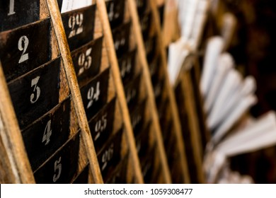 Numbered old and faded time clock punch card wall rack with papers in the distance