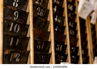 Numbered old and faded time clock punch card wall rack with paper in the distance