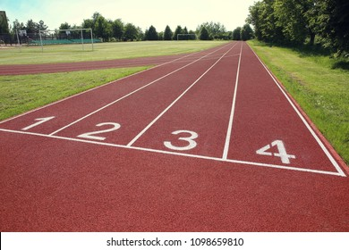 Numbered start track in stadium. Start line with numbers and lanes on running track in school stadium.