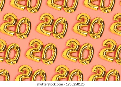 Numbers 20 golden balloons pattern. Twenty years anniversary celebration layout on a coral background.