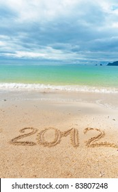 Numbers 2012 on tropical beach sand - holiday background