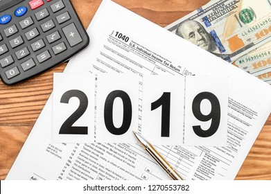 Numbers 2019 with tax form, calculator and money on the table. Top view.