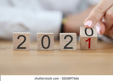 Numbers 2020 make up wooden cubes in row. Female hand turn number 2020 into number 2021 with her finger. - Shutterstock ID 1826897666
