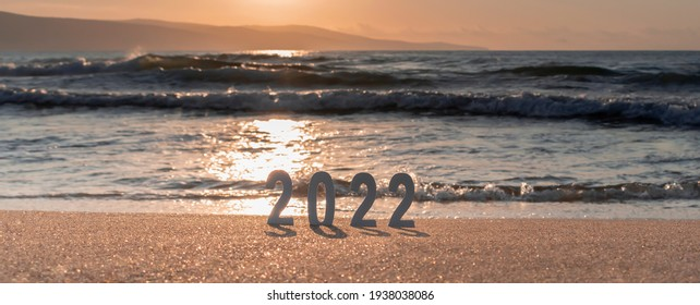 Numbers 2022 on golden sand of beach and blurry sea sunrise or sunset. New Year's vision, dreams, goals concept. New Year's Eve travel. Banner for web, selective focus, copy space