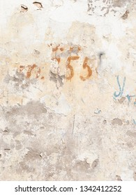 numbers fifty five on old wall with peeling paint on the street