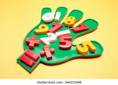 Numbers on Plastic Hand on Yellow Background