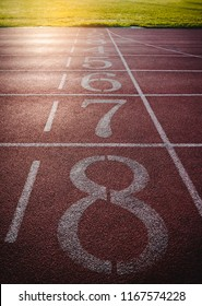 Numbers on running track with green grass in stadium, color is orange brick. Start and finish point of athletic track. Outdoor with sunlight on summer day. Sport Background. Vintage film filter effect