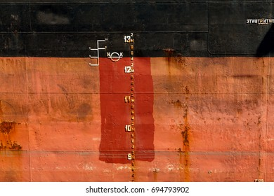 Numbers on waterline of ship. Waterline, marked on board dry cargo ship, ship with rough draft scale. Indication of workload at level of waterline on board vessel.