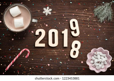 numbers on wooden background with winter decoration,  symbolizng the change from 2018 to 2019