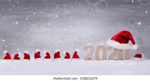 the numbers for the year 2020 in the deep snow with a big santa claus hat on top and a row of little hats next to it, with a grey sky background like a chistmas winter sky with shining stars and snow