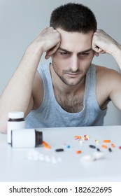 Numbing his soul. Frustrated young man sitting at the table and looking at the pills laying on it