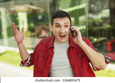 Numbing news. Wondering handsome man hearing happy numbing news which hearing when using smartphone