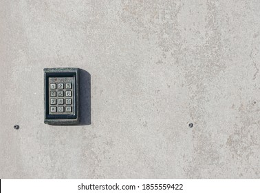 numeric keypad on concrete wall