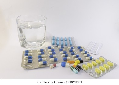 Numerous colorful and vivid drugs in form of tablet,capsule isolated on white background with drinking water glass